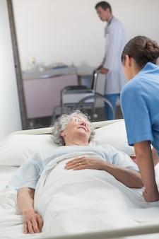 Infermiera che si occupa di un paziente anziano
