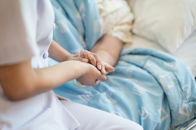 Infermiera che si siede su un letto di ospedale accanto ad una donna più anziana che aiuta le mani, si preoccupa per il concetto anziano