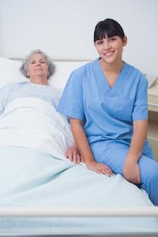 Infermiera che si siede su un letto medico