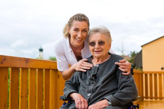Infermiera dei giovani e senior femminile in una sedia a rotelle