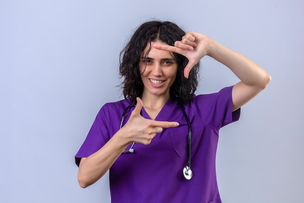 Infermiera della giovane donna in uniforme medica e con lo stetoscopio che fa un gesto della struttura con le mani