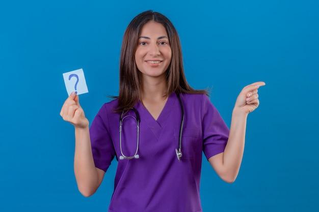 Infermiera donna in uniforme medica e con uno stetoscopio tenendo la carta promemoria con un punto interrogativo molto felice indicando con la mano e il dito a lato in piedi sul blu