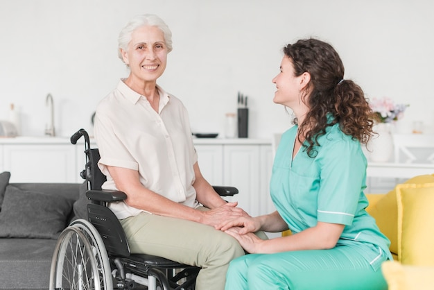 Infermiera femminile che esamina paziente disabile che si siede sulla sedia a rotelle