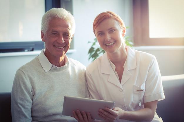 Infermiera femminile che mostra referto medico all'uomo senior sulla compressa digitale