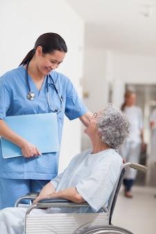 Infermiera in piedi accanto a un paziente in una sedia a rotelle