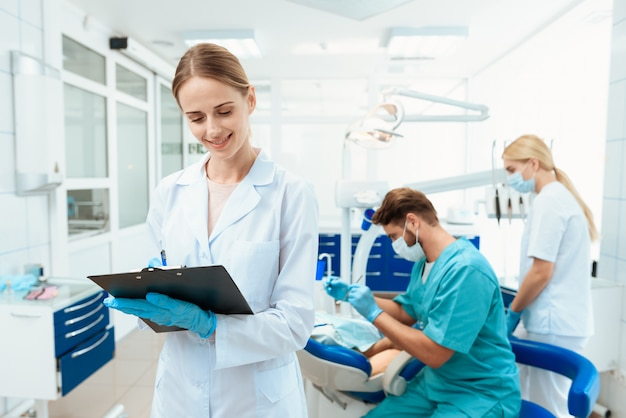 Infermiera in posa su uno sfondo di dentisti
