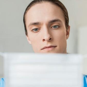 Infermiera maschio del primo piano con la mascherina medica