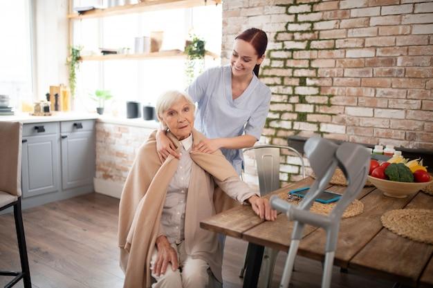 Infermiera premurosa che mette plaid sulle spalle della donna invecchiata