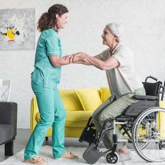 Infermiera sorridente che aiuta paziente femminile senior a uscire dalla sedia a rotelle