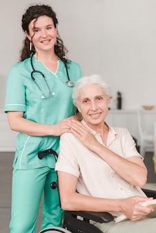 Infermiera sorridente che dà supporto al paziente senior femminile che si siede in sedia a rotelle