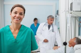 Infermiera sorridente che si leva in piedi in una stanza di ospedale