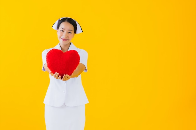 Infermiera tailandese della bella giovane donna asiatica del ritratto con figura del cuscino del cuore