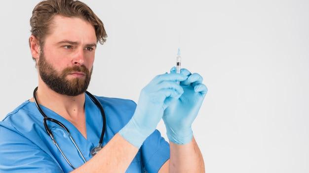 Infermiera uomo in uniforme e guanti in possesso di iniezione