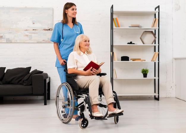 Infermiere prendersi cura della donna in sedia a rotelle