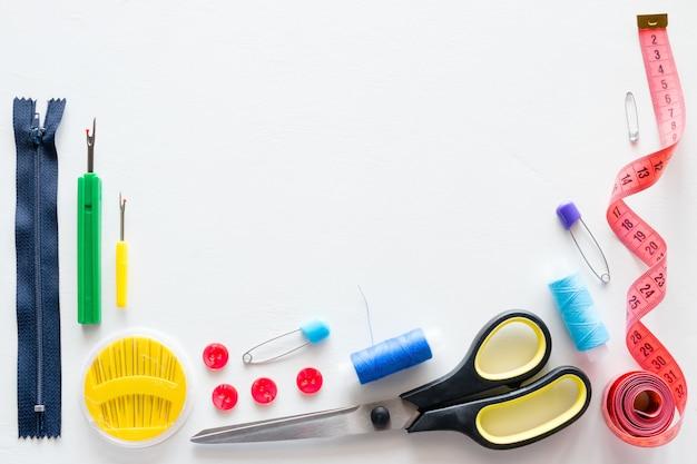 Infili e accessori di cucito su bianco con il posto per testo