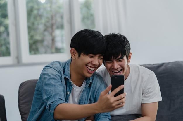 Influencer asiatico coppia gay vlog a casa. gli uomini asiatici lgbtq si rilassano felici utilizzando la tecnologia di telefonia mobile record di stile di vita video vlog upload nei social media mentre giace divano nel soggiorno.