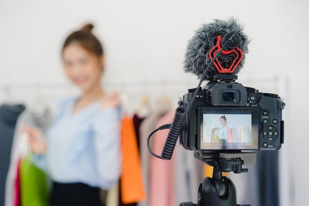 Influencer online di blogger femminile della moda asiatica che tiene i sacchetti della spesa e molti vestiti