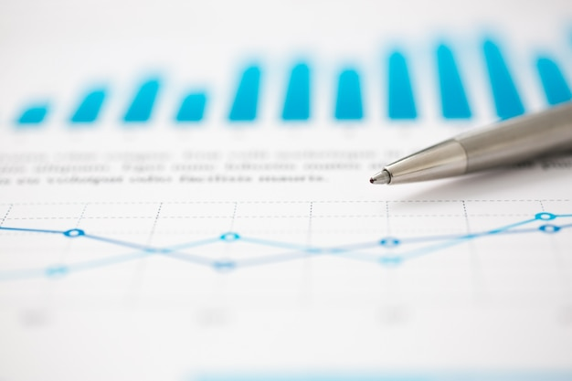 Infographics finanziario della penna a sfera dei documenti di statistiche alla tavola dell'ufficio