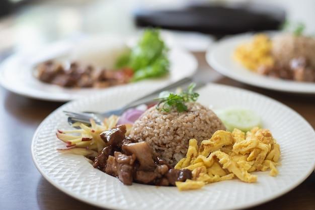 Inforni il riso con la carne di maiale e l'uovo di fuoco sulla tavola di legno