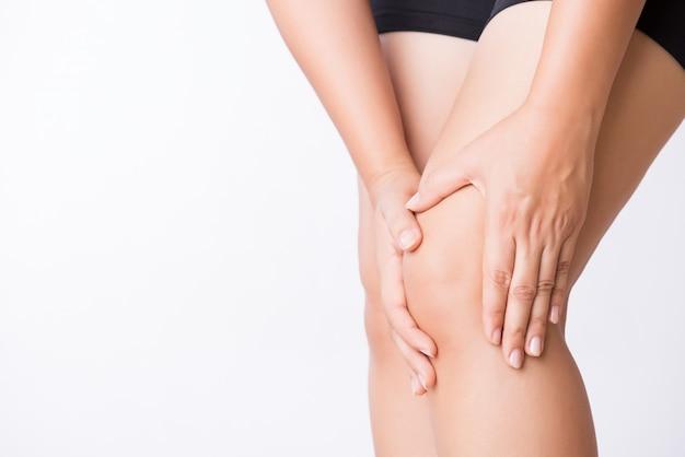 Infortunio al ginocchio sportivo runner. giovane donna del primo piano nel dolore del ginocchio mentre correndo