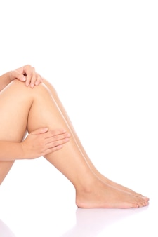 Infortunio al ginocchio. tenuta della donna sulla sua gamba isolata sopra fondo bianco