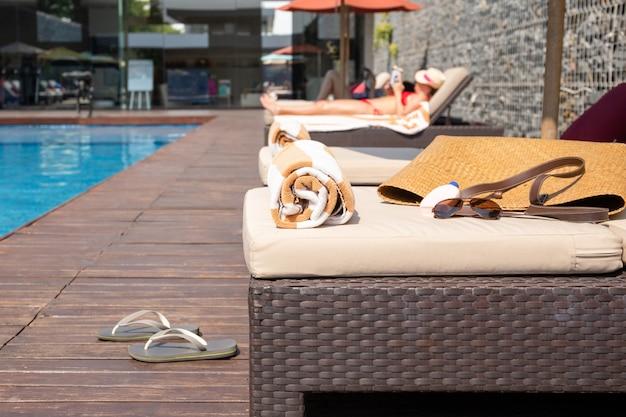 Infradito, asciugamano, crema solare con borsa da spiaggia sul lettino a bordo piscina.