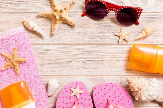 Infradito, cappello di paglia, stelle marine, bottiglia di crema solare, spray per lozione per il corpo sulla vista superiore del fondo di legno. spiaggia piatta estate spiaggia accessori mare sfondo, concetto di viaggio