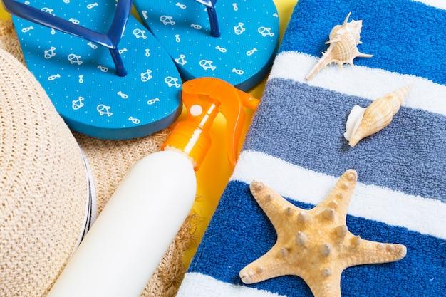 Infradito, cappello di paglia, stelle marine, flacone di crema solare e spray per lozione per il corpo