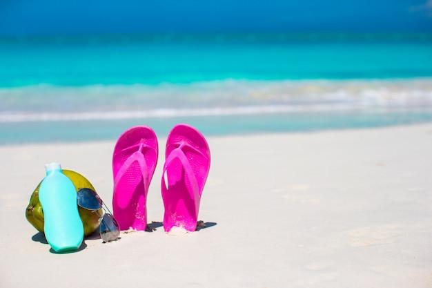 Infradito, cocco e crema solare sulla sabbia bianca. accessori da spiaggia.