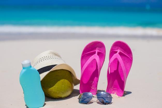 Infradito, cocco e crema solare sulla sabbia bianca