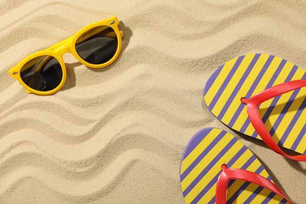 Infradito e occhiali da sole sulla sabbia del mare, spazio per il testo