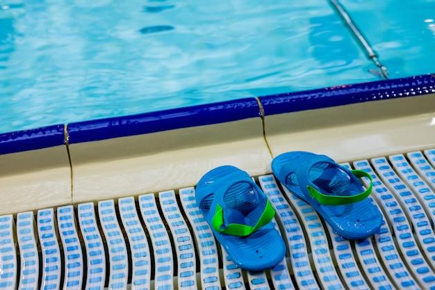 Infradito sulla piscina, sfondo estivo con spazio di copia. vacanze estive in un resort. accessori estivi in piscina, concetto di viaggio, tempo di vacanza. ciabatte, coppia di bambini blu infradito