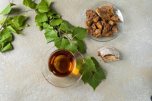 Infuso curativo di funghi di betulla con pezzi di chaga in una ciotola. caffè o tè ai funghi chaga.