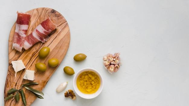 Infuso di olio d'oliva; olive; club dell'aglio; formaggio e pancetta isolati su sfondo bianco