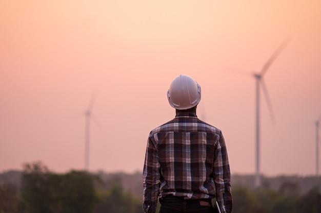 Ingegnere africano che indossa casco bianco che sta con la compressa digitale contro il generatore eolico il giorno soleggiato