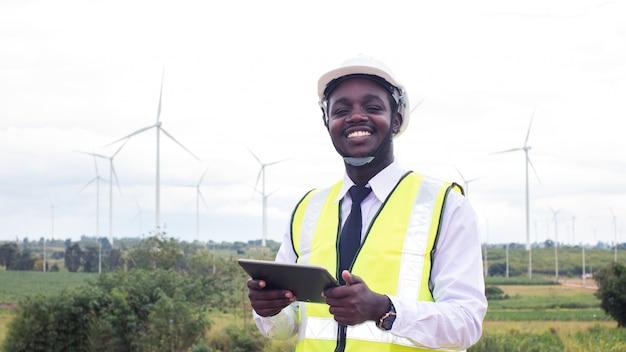 Ingegnere africano in piedi e hoding laptop con turbina eolica