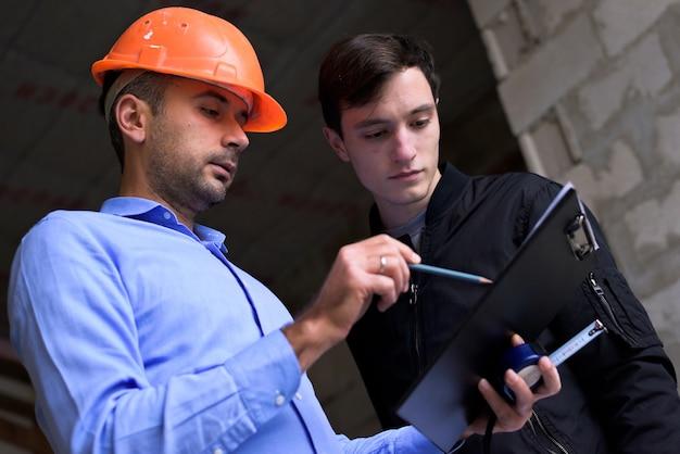 Ingegnere architetto che indossa un casco arancione sul luogo di lavoro che spiega i piani del progetto al cliente