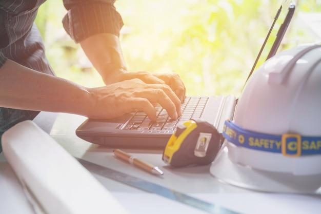 Ingegnere architetto con laptop per lavorare con casco bianco, computer portatile e caffè