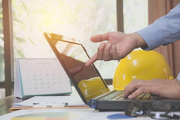 Ingegnere architetto con laptop per lavorare con il casco giallo sulla scrivania.