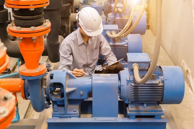 Ingegnere asiatico che controlla la pompa dell'acqua del condensatore