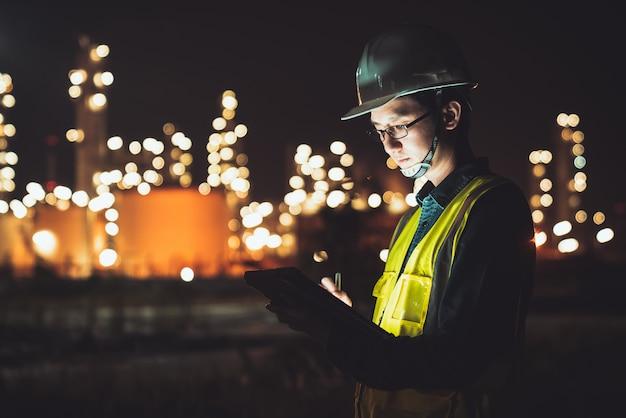 Ingegnere asiatico che utilizza compressa digitale che lavora tardi alla raffineria di petrolio nella zona industriale