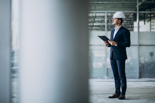 Ingegnere bello dell'uomo di affari in casco in una costruzione