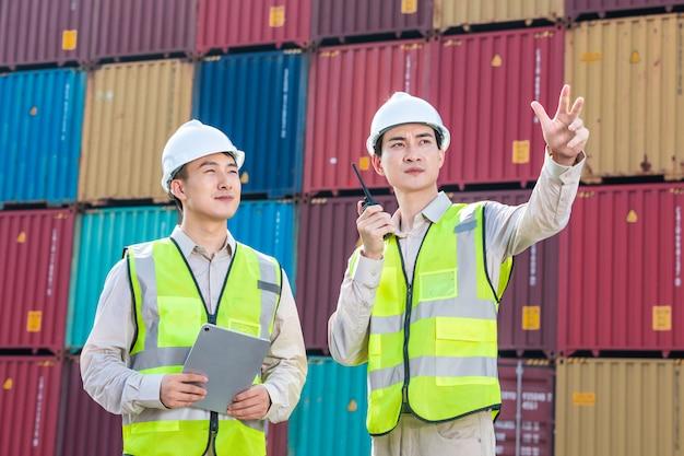 Ingegnere che controlla il contenitore di carico di carico dall'esportazione di importazione di navi da carico