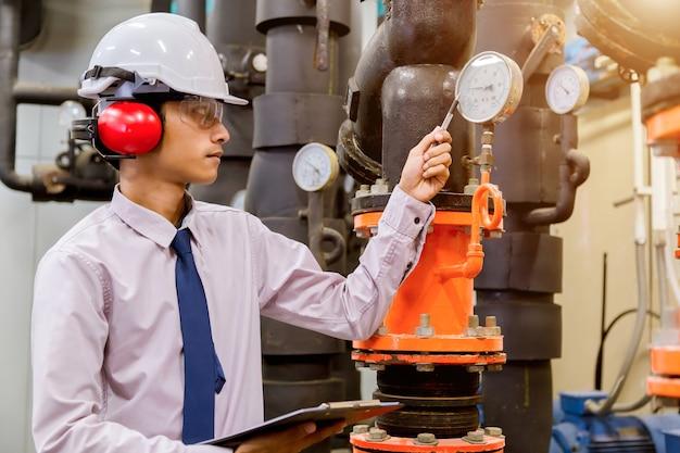 Ingegnere che controlla la pompa dell'acqua del condensatore e il manometro.