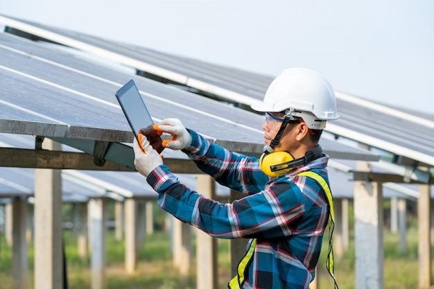 Ingegnere che lavora al controllo e all'attrezzatura di manutenzione a energia solare di industria, concetto di nuova energia verde.