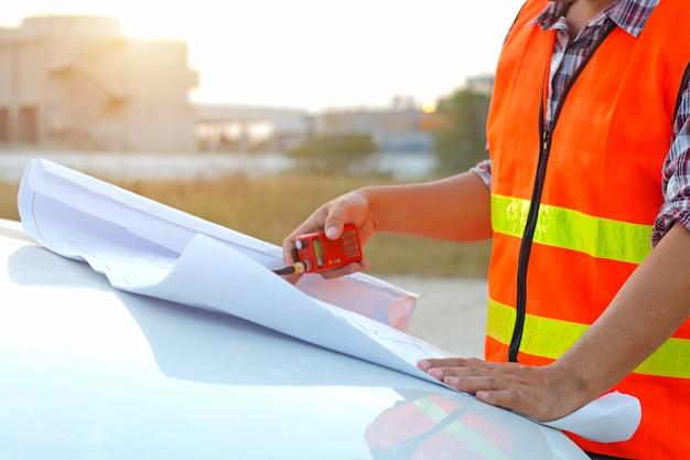 Ingegnere che lavora al piano di controllo esterno sul cantiere