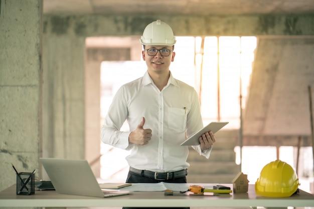 Ingegnere che lavora con il computer portatile circa il piano di costruzione in loco