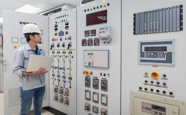 Ingegnere che lavora e controlla la distribuzione dell'energia elettrica del quadro di stato nella sala della sottostazione della centrale elettrica