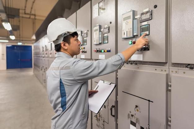 Ingegnere che lavora e controlla la distribuzione dell'energia elettrica del quadro di stato nella sala sottostazione