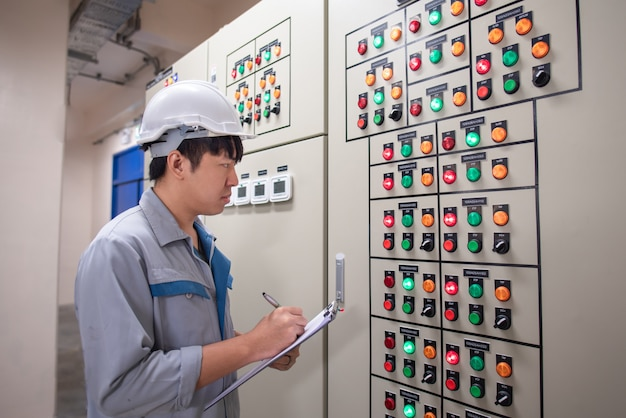 Ingegnere che lavora e controlla lo stato del quadro elettrico nella stanza hvac